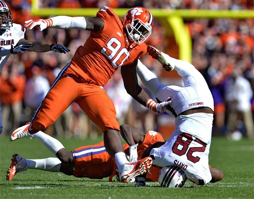 South Carolina running back Mike Davis is upended by Clemson's Mackensie Alexander and Shaq Lawson (90) during the first half of an NCAA college football game in Clemson, S.C., Saturday, Nov. 29, 2014. (AP Photo/Richard Shiro)
