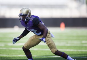 UW FOOTBALL PRACTICE -- 140982 -- 08/16/2014 Former Bellevue star, defensive back Budda Baker, gets low as he participates in warmups with the rest of the University of Washington Huskies during practice at Husky Stadium on Saturday, Aug. 16, 2014. The 2014 team currently does not have a starting quarterback chosen out of the four available to them. Troy Williams, Jeff Lindquist, K.J. Carta-Samuels and Cyler Miles will all be competing for the position.