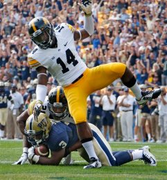 Pitt running back Chris James (3) scores a first-quarter touchdown as Iowa defensive back Maurice Fleming (28) makes the late tackle in the endzone, and Iowa defensive back Desmond King (14) leaps over them during an NCAA college football game in Pittsburgh, Saturday, Sept. 20, 2014. (AP Photo/Gene Puskar)